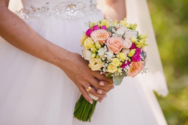 花嫁の手にクリーム色のバラとトルコギキョウの花の美しい優しい結婚式の花束