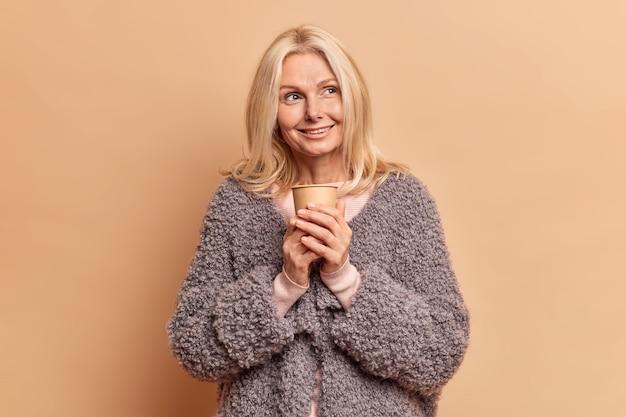 아름 다운 부드러운 여자는 커피 종이 컵 휴식 포즈에 대한 사려 깊은 표정이 멀리 보이는 것을 기쁘게 생각하고 베이지 스튜디오 벽에 향기로운 음료 스탠드를 마시는 것을 즐깁니다.