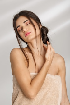 Beautiful tender woman with eyes closed, stroking neck with finger.