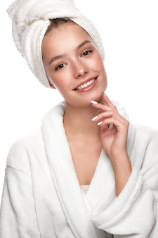 Красивая нежная молодая девушка в белом полотенце с чистой свежей кожей позирует перед камерой. красота лица. забота о коже. снимок сделан в студии на белом фоне изолировать.