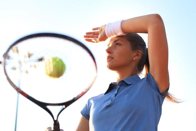 Beautiful tennis player serving the ball on the tennis court.