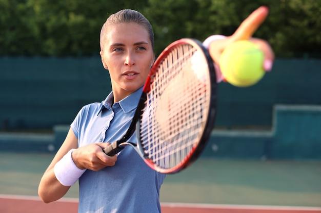 테니스 코트에서 공을 제공하는 아름다운 테니스 선수.