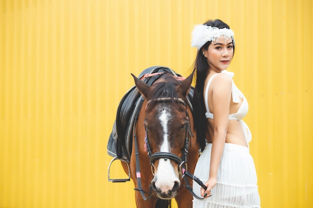 A beautiful thai asian woman wearing a white dress is standing next to a horse with a yellow background.