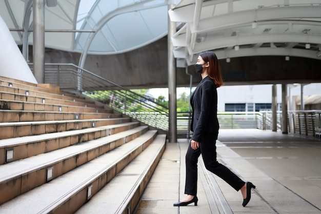 Красивая тайская бизнес-леди из азии. она готова подняться по лестнице на работу в бангкок, таиланд, одетая в черный костюм.