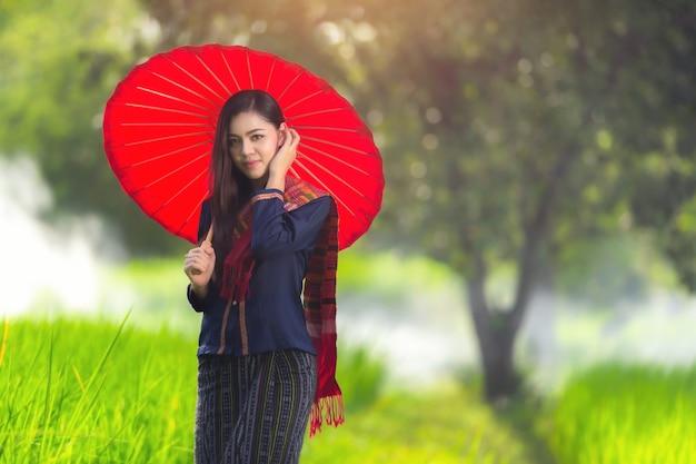 伝統的なドレスの衣装赤い傘の美しいタイの女の子。