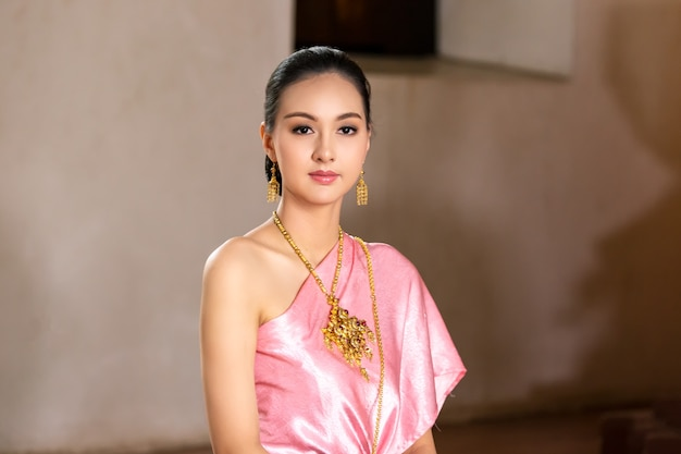 Beautiful thai girl in pink traditional dress costume of thailand at thai temple place.