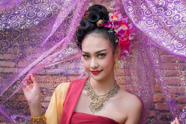 Beautiful thai girl in traditional dress costume in choeng tha as thai temple