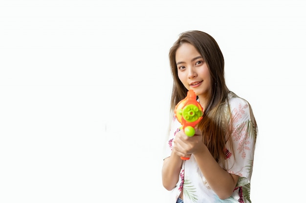 A beautiful thai woman smiling fresh and happy, in her hand holding a water gun in the thai songkran festival on a white background.