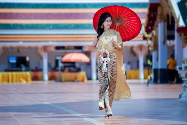 Beautiful thai woman in traditional dress costume in phra that choeng chum thailand temple