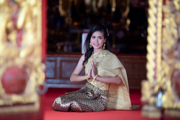 Beautiful thai woman in traditional dress costume, temple thailand