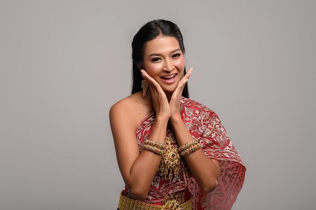 Красивая тайская женщина нося тайское платье и счастливую улыбку.