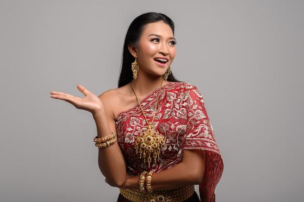 Красивая тайская женщина, носящая тайское платье и смотрящая наверх
