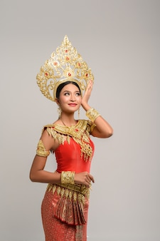 Beautiful thai woman wearing thai dress and looking at the top