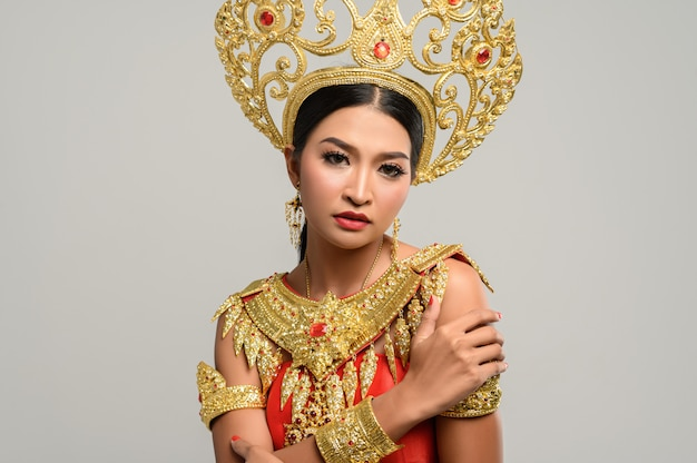 Beautiful thai woman wearing thai dress and standing hugging herself