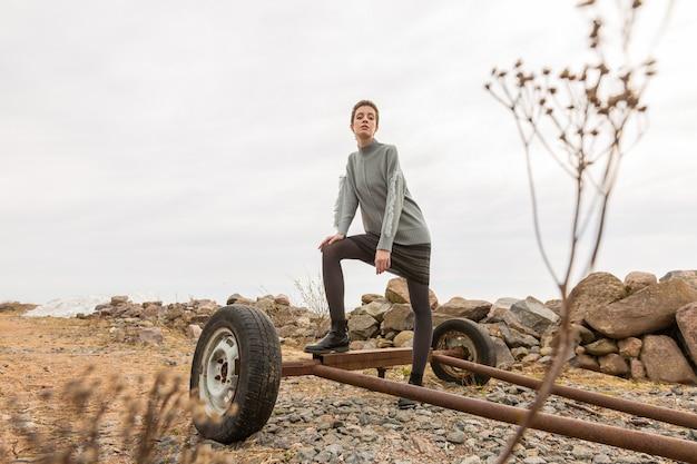 灰色のセーターと古いワゴンの田舎でポーズをとる暗いスカートの美しい薄いモデル。