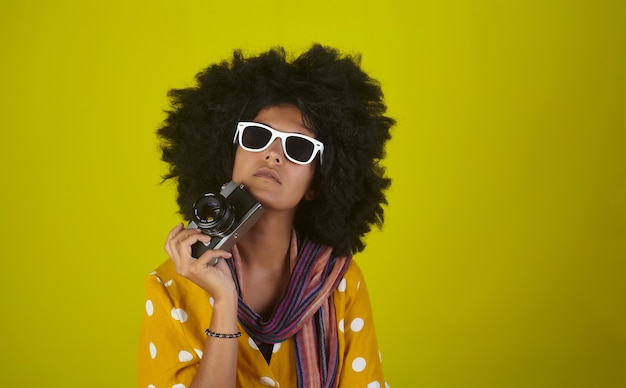 黄色の壁に彼女のレトロなカメラを保持しているアフロの巻き毛のヘアスタイルを持つ美しい思考の女の子