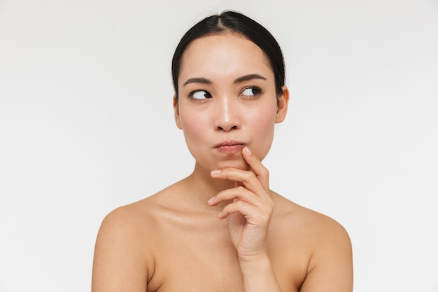 白い壁の上に孤立した裸でポーズをとる健康な肌を持つ美しい思考の若いかなりアジアの女性。