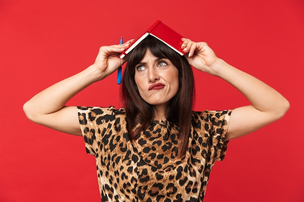 Beautiful thinking young woman dressed in animal printed shirt posing isolated over red wall with notebook on head.