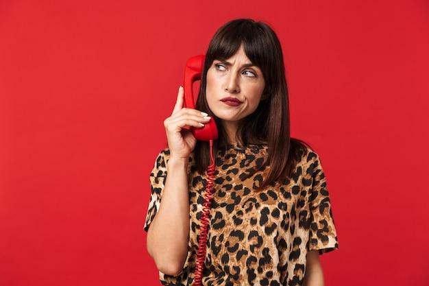 電話で話している赤い壁の上に隔離されたポーズでポーズをとるアニマルプリントのシャツに身を包んだ美しい思考の若い女性。