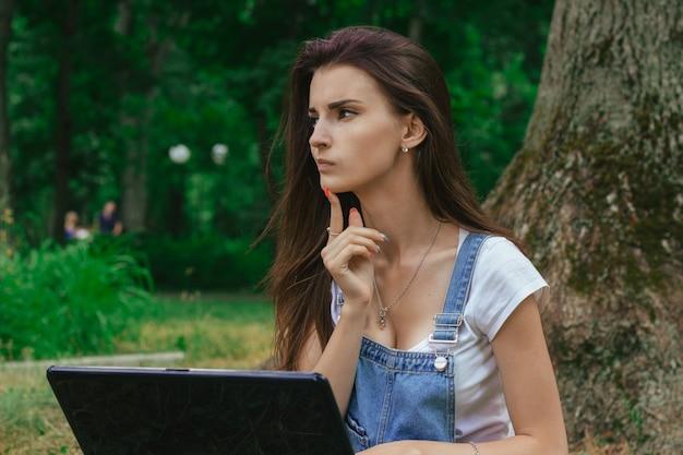 Красивая задумчивая дама с ноутбуком в парке крупным планом