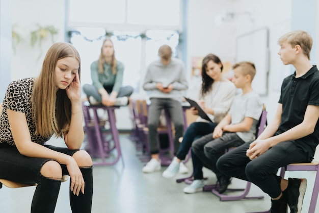 Beautiful thoughtful teenage girl sits on the side of a class during lesson at school