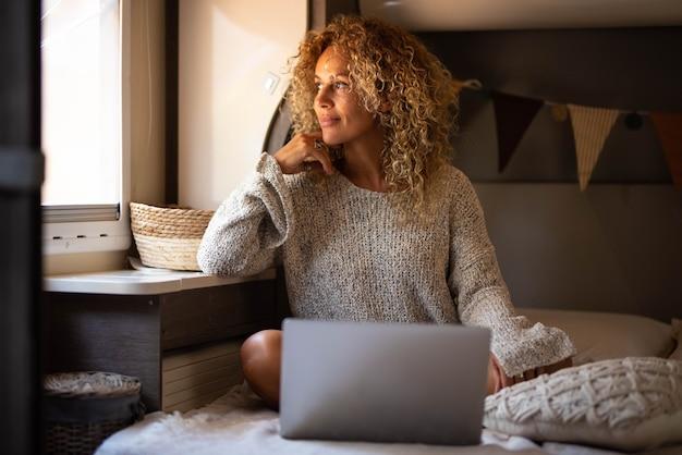 巻き毛とニットトップの空想やアイデアを考えている美しい思慮深い女性、自宅のラップトップで居心地の良いベッドに座って窓から外を眺めながら良い未来の計画