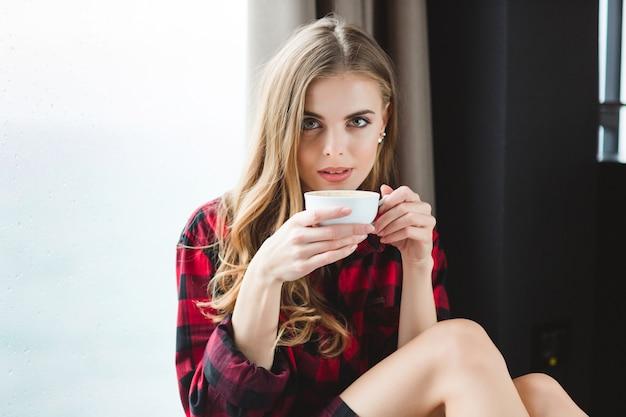 Красивая вдумчивая молодая женщина в клетчатой рубашке пьет кофе по утрам