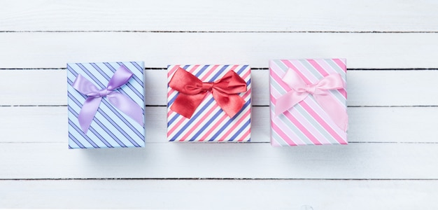 Beautiful three gifts boxes presents on white wooden background