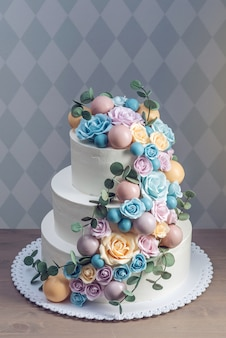 Beautiful three-tiered white wedding cake decorated with colorful flowers roses