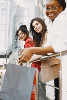 Belle tre giovani donne con borse regalo camminano per la città. le donne dopo lo shopping si divertono.