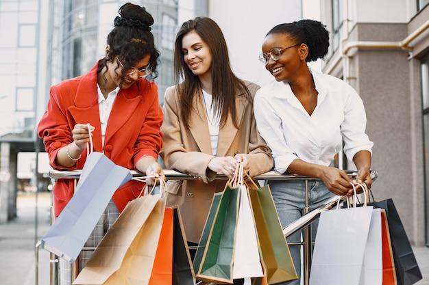 Belle tre giovani donne con borse regalo camminano per la città