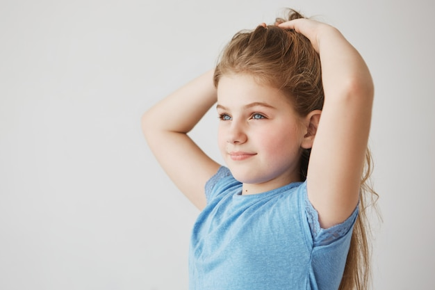 Bella ragazza minuscola con affascinanti occhi azzurri e lunghi capelli chiari sorrisi, guardando da parte e facendo acconciatura. concetto di infanzia, infanzia e stile di vita.