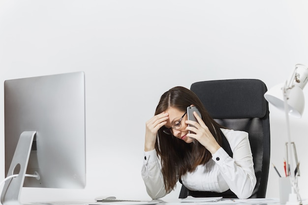 机に座って、軽いオフィスでドキュメントを使って現代のコンピューターで働いて、携帯電話で話し、問題を解決するスーツを着た美しい疲れてストレスのビジネスウーマン
