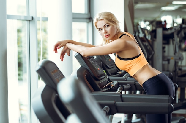 Beautiful tired blond woman on treadmill in gym after workout.