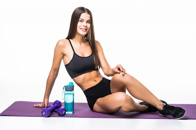 Beautiful tired sportswoman with water bottle while resting on the floor isolated on gray