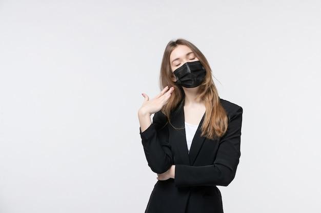 Bella giovane donna stanca in tuta che indossa una maschera chirurgica su bianco