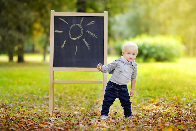Beautiful toddler boy drawing standing by a blackboard outdoors
