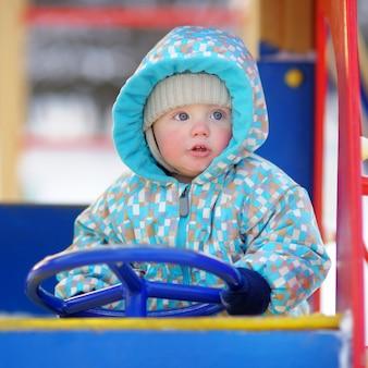 Beautiful toddler boy having fun on playground