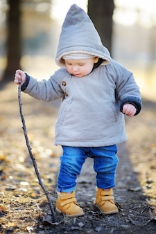 Beautiful toddler boy walking outdoors at the warm spring day