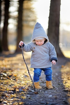 Beautiful toddler boy walking and playing outdoors at the warm spring day