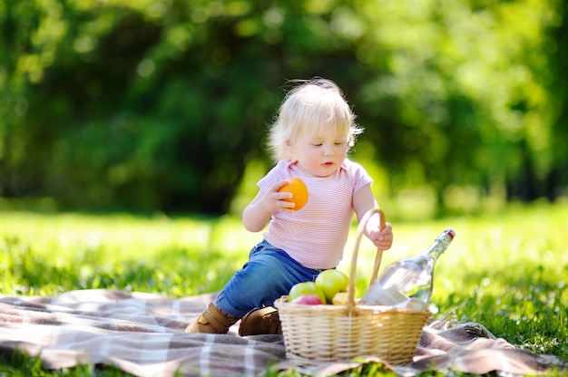 Beautiful toddler child having a picnic in sunny park