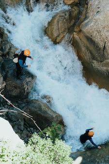 美しいトップ アングル ショットは、石の多い山の川の上でエクストリーム スポーツをしている人々