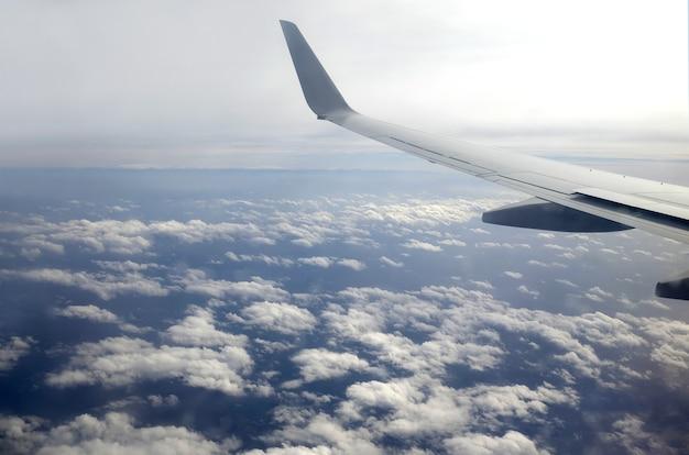 Красивый вид сверху из окна пассажирского сверхзвукового самолета, летящего высоко над белыми облаками в голубом небе