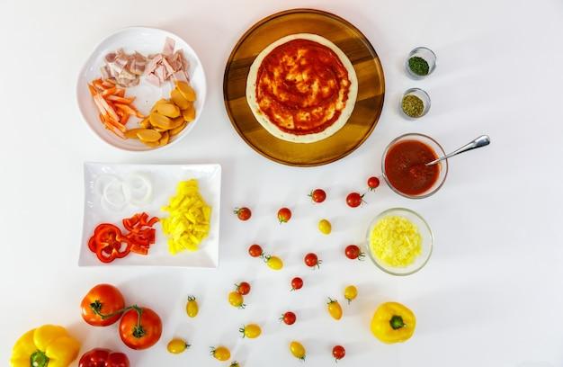 Красивый вид сверху блюд с различными ингредиентами для приготовления вкусной здоровой пиццы, выровненной на белом столе, таких как ветчина, хот-дог, крабовая палочка, луковое кольцо, помидоры, болгарский перец, ананас, кетчуп, приправы