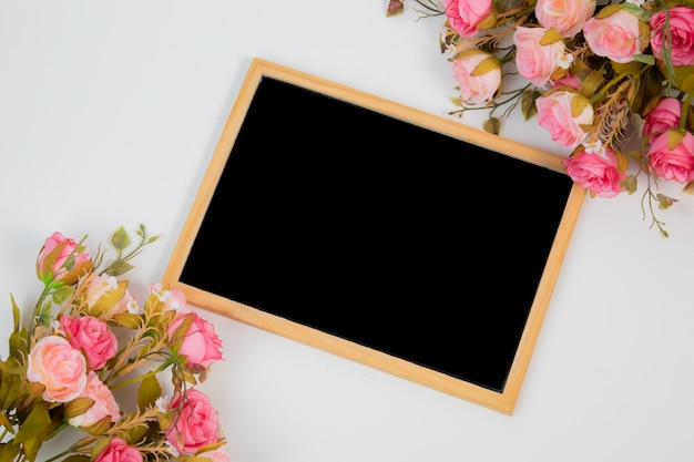 Beautiful top view wedding background concept with chalkboard frame and flower decorations