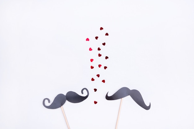 Beautiful toppings with a man's moustache on a gray background with hearts. concept of homosexual relations
