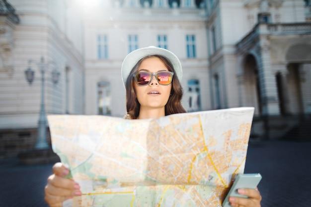 帽子とサングラスをかけ、古いヨーロッパの都市で地図と携帯電話を持って、旅行、ヨーロッパで巻き毛の美しい観光客の女の子。