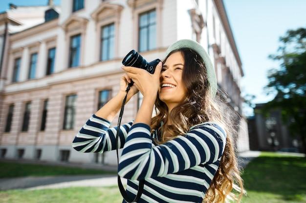사진을 만들고 오래 된 유럽 도시, 여행, 초상화, 사진에 웃 고 모자를 쓰고 곱슬 머리를 가진 아름 다운 관광 소녀.