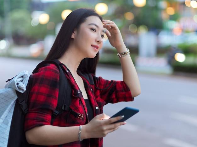 애플리케이션에서 스마트폰 예약 택시를 들고 거리에서 택시를 찾는 아름다운 관광객