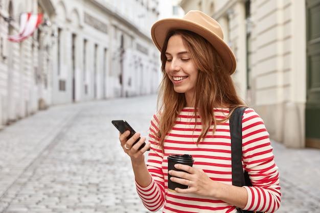 美しい観光客は街の通りを散歩し、正しい道を見つけるためにオンラインナビゲーターを使用し、携帯電話を持っています